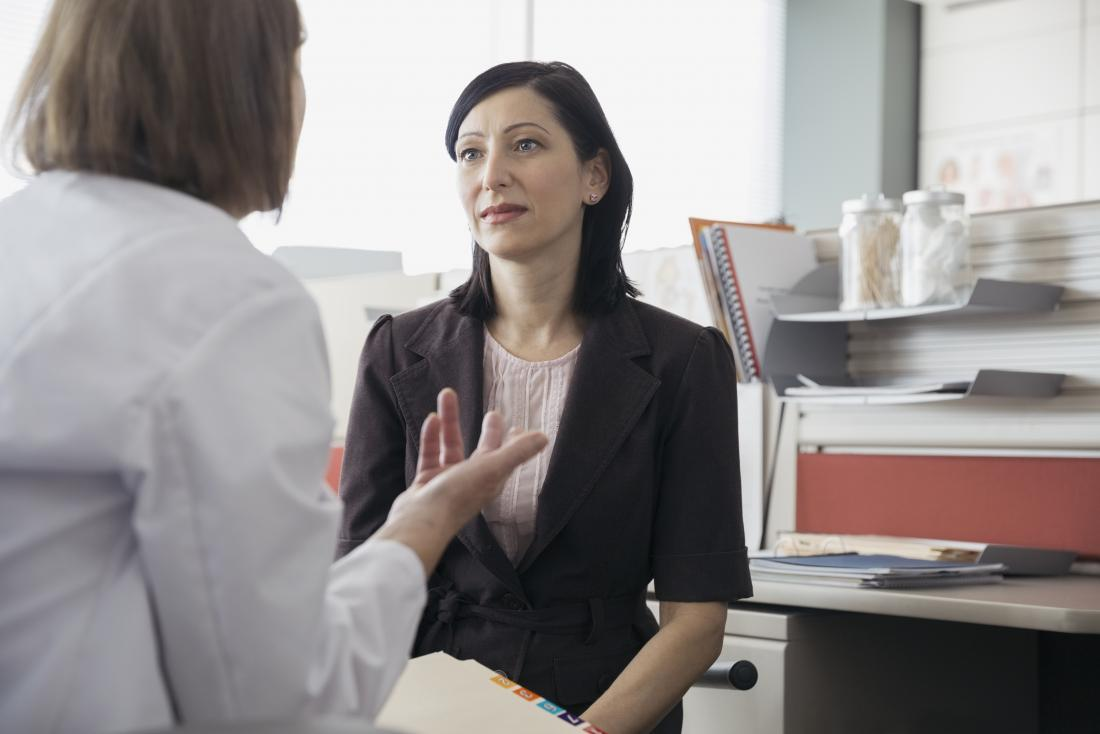 Female patient listening to woman doctor in office