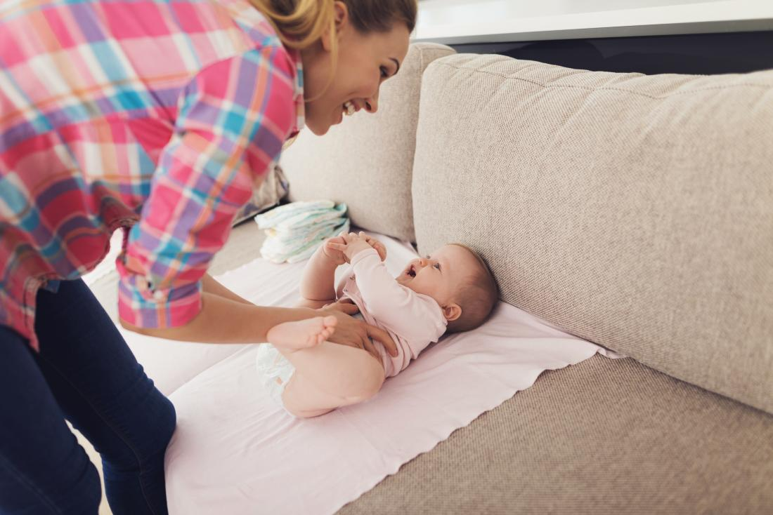 Mother changing smiling and laughing baby on couch