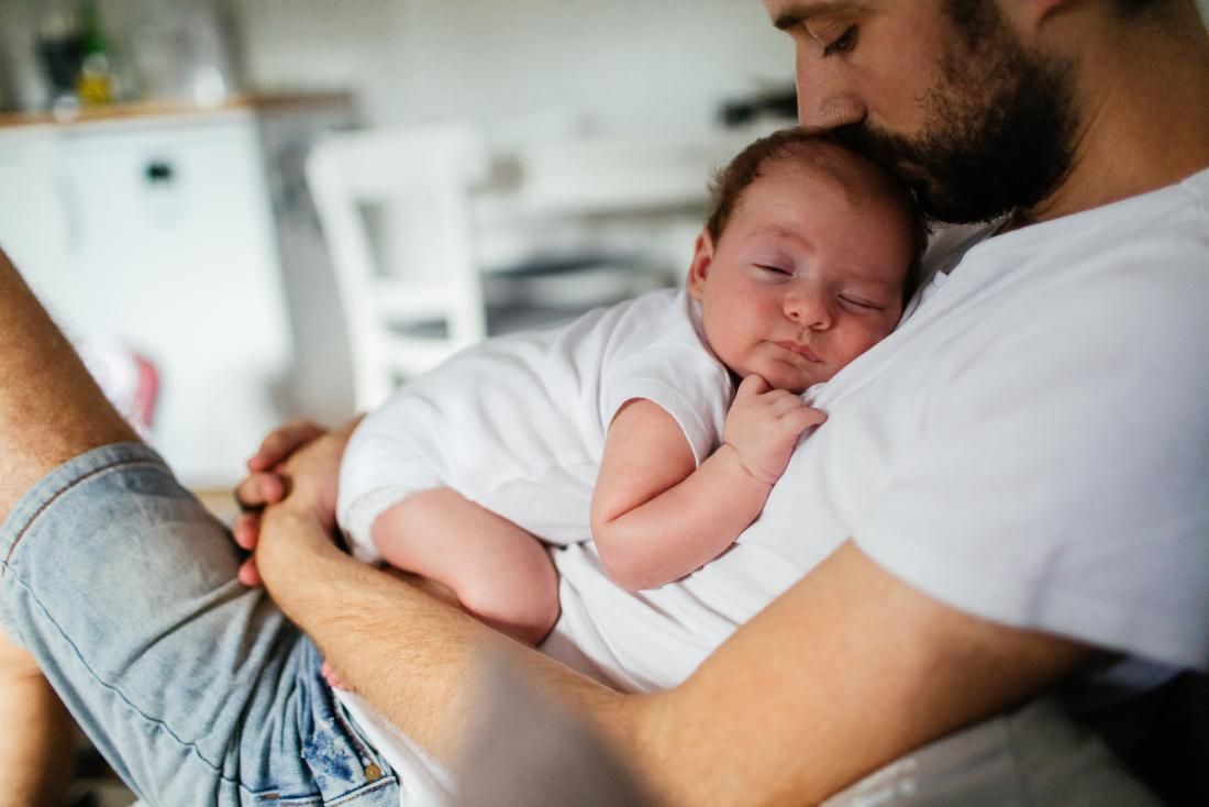 Father sitting while holding sleeping baby