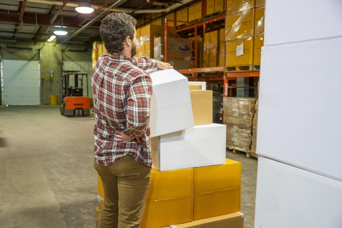 Man working in warehouse holding lower right back in pain