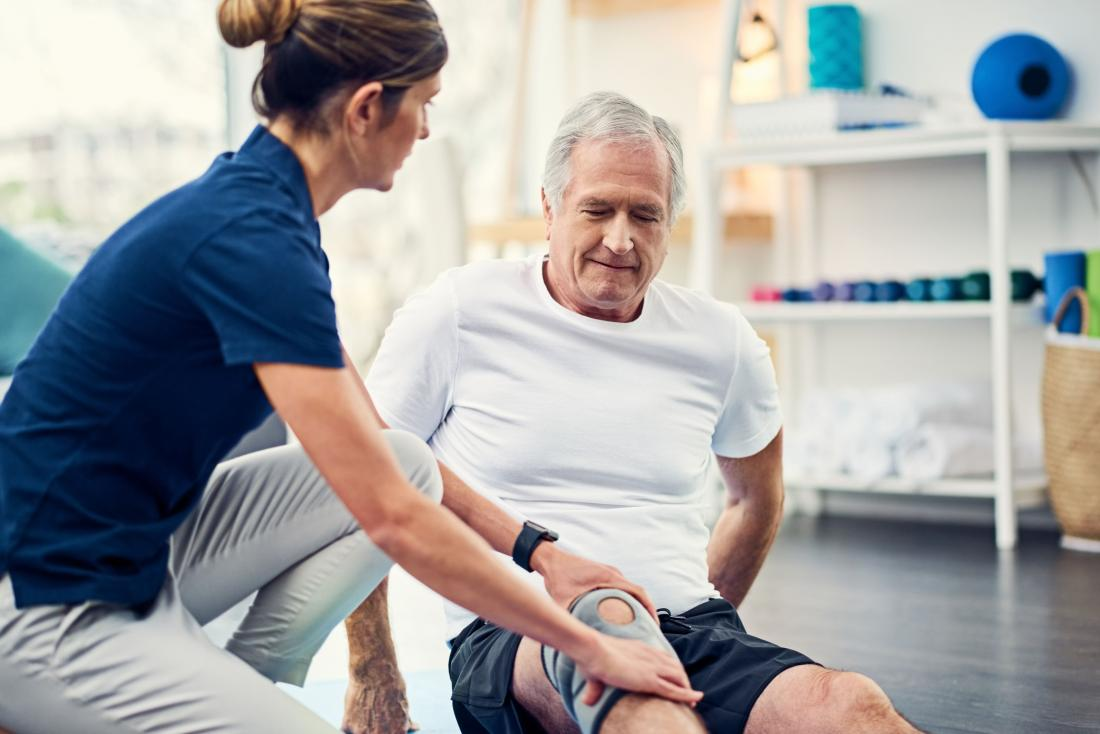Senior man with knee brace having physical therapy