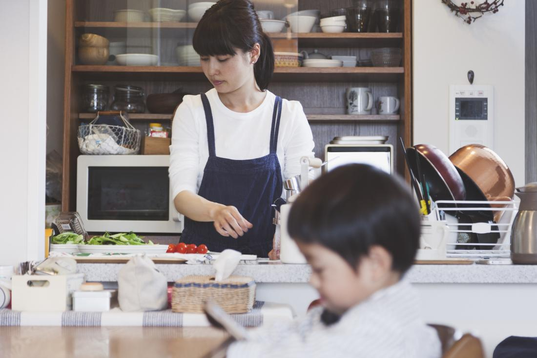 Woman preparing food in kitchen for cooking recipe while child in foreground plays on tablet
