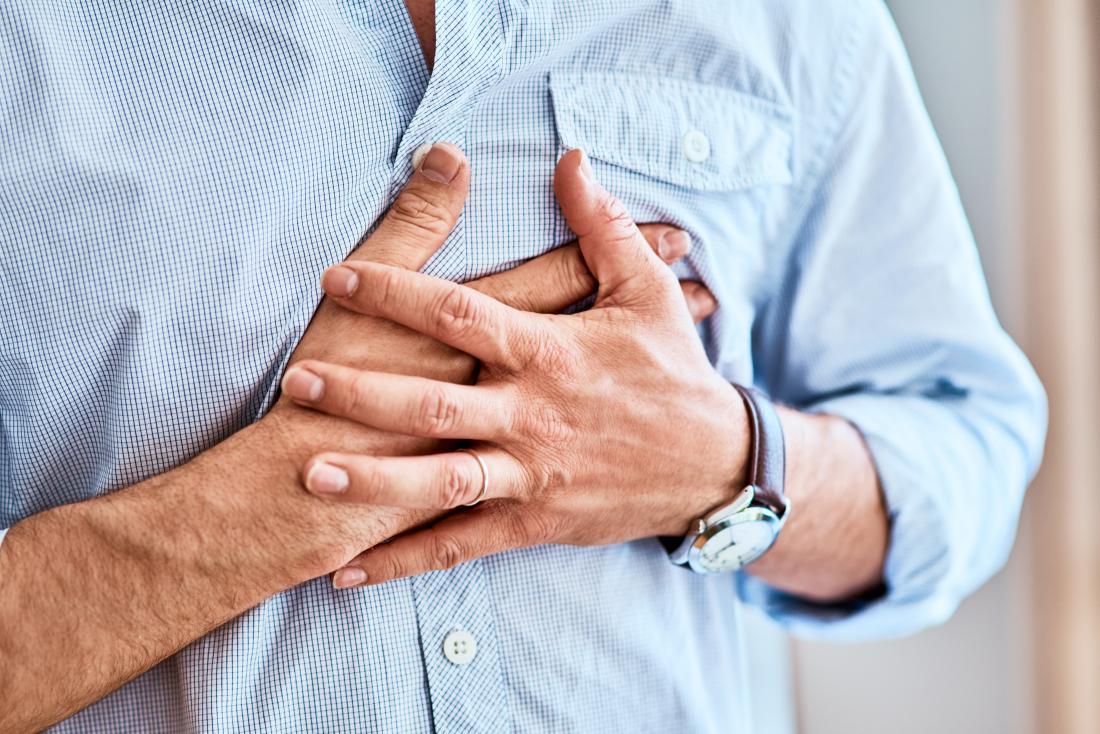 Man clutching his chest in pain because of heart attack