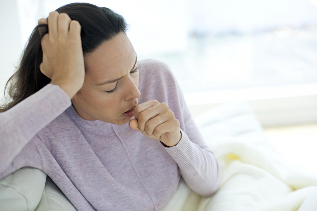 Ill woman coughing into fist