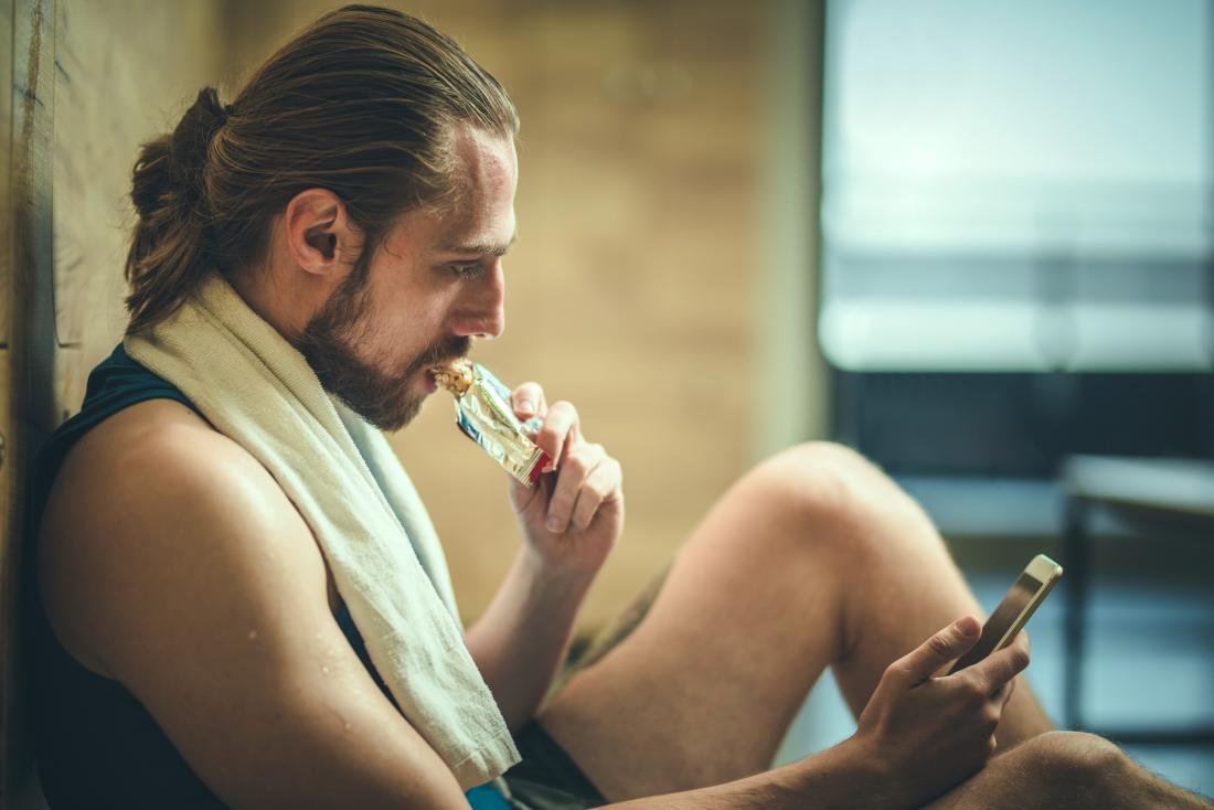 Man in gym eating protein nutrition bar while looking at phone, sitting on floor with towel around neck after fitness and exercise