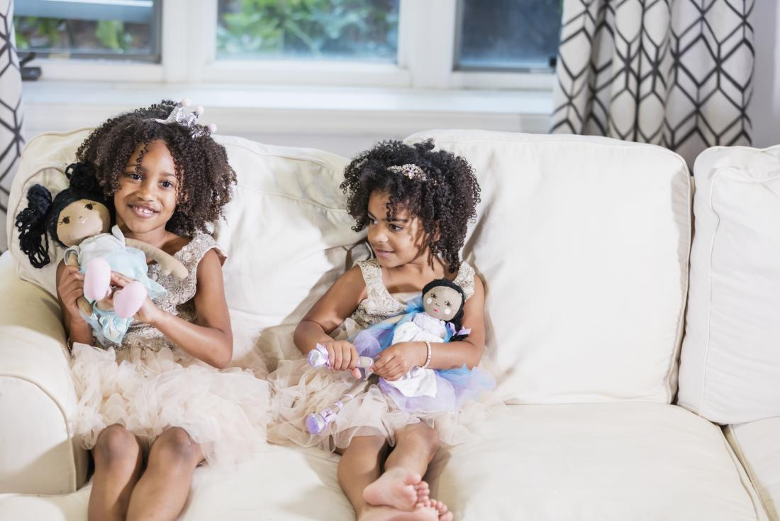 two girls in tutus holding rag dolls