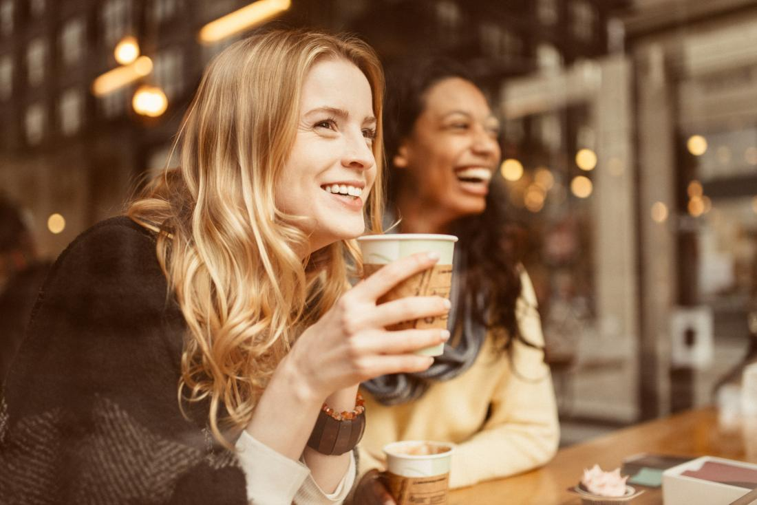 woman smiling drinking a cup of coffee