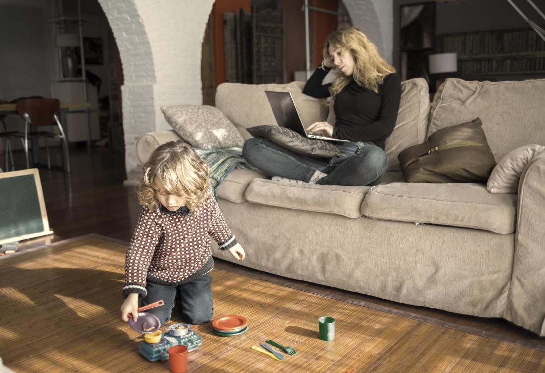 mother on sofa with child playing on the floor