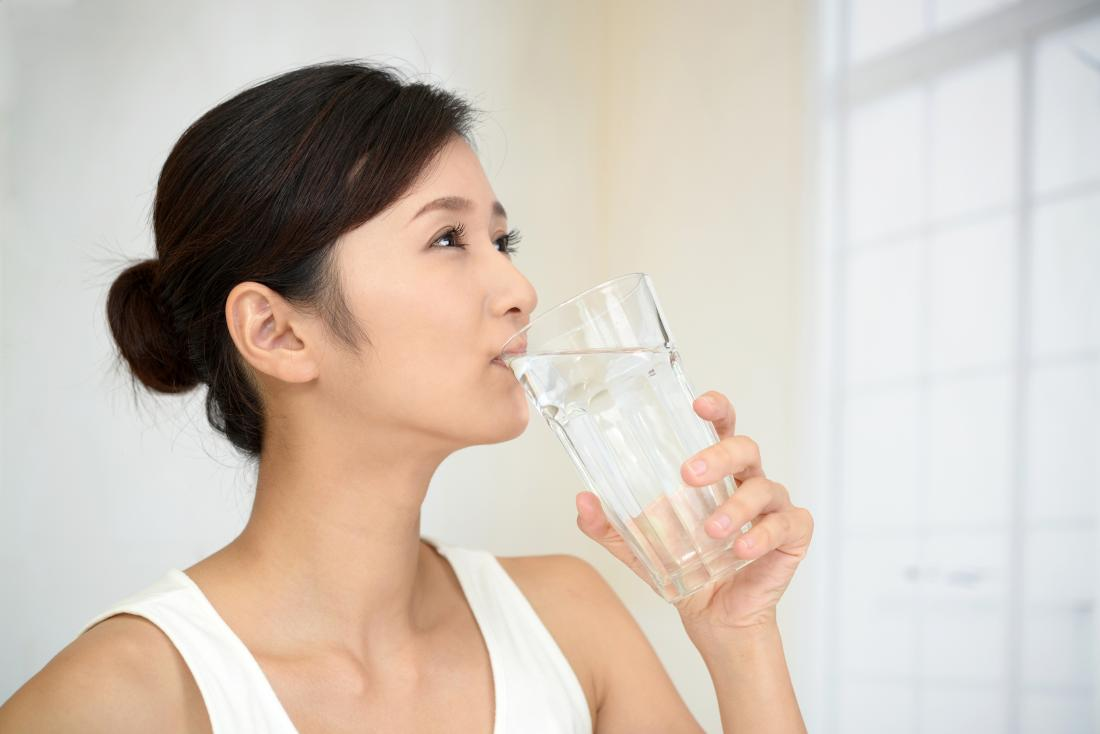Woman drinking water which is a home remedy for gout