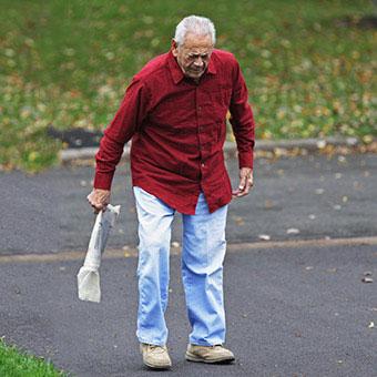 A man with rheumatoid arthritis (RA) limps after retrieving his newspaper.