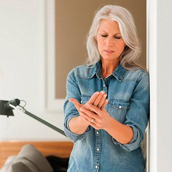 A woman suffers hand pain due to rheumatoid arthritis (RA).