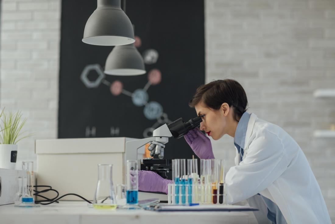 scientist looking through microscope