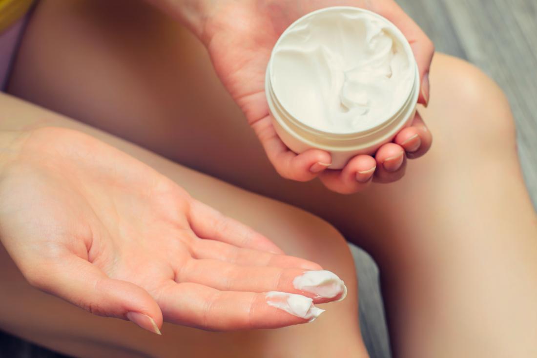 Woman holding a pot of cream