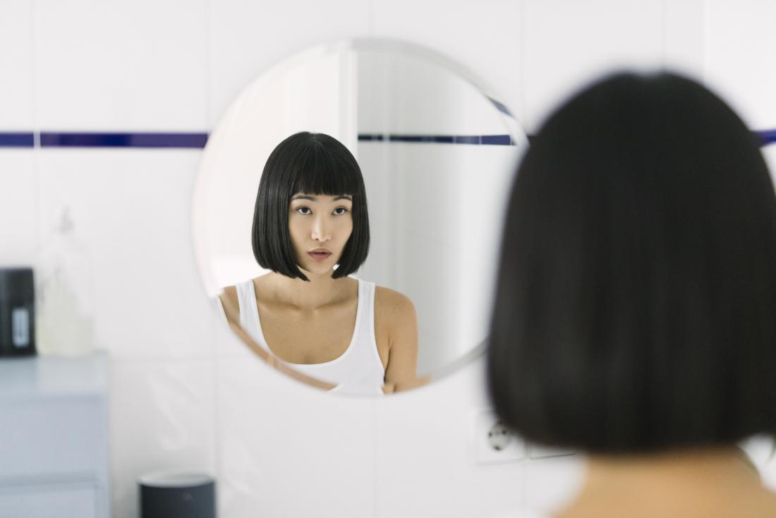 Woman looking in the mirror in the bathroom, slightly concerned about dry nipples