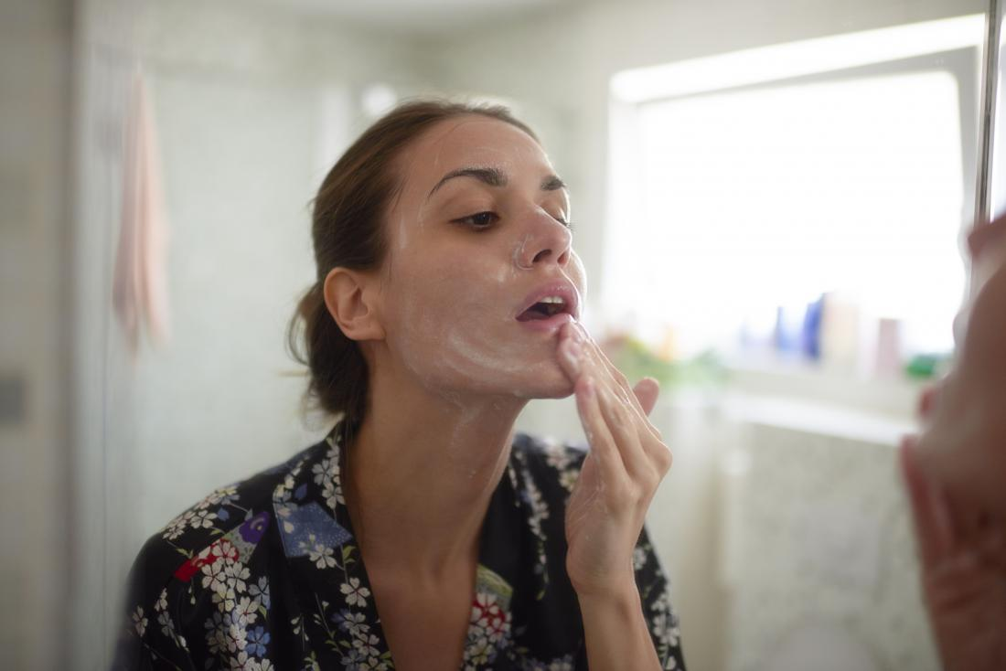 Woman washing face looking in bathroom mirror