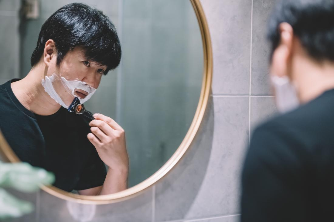 Asian man looking in bathroom mirror shaving