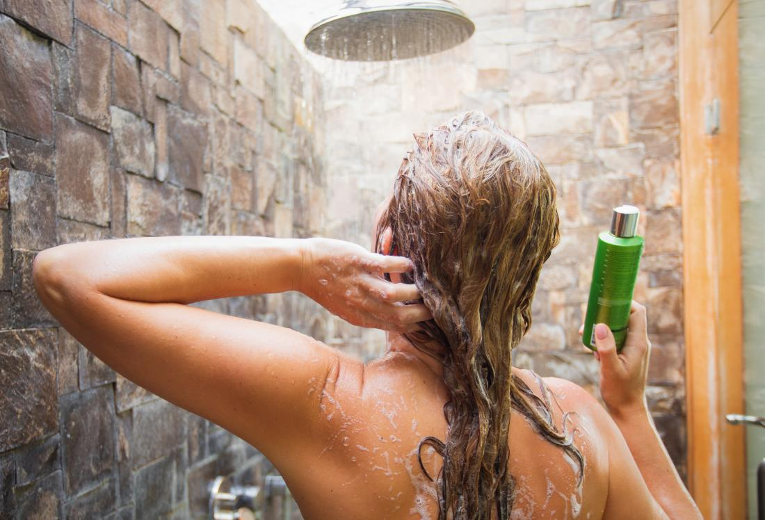 Woman in the shower using a conditioner