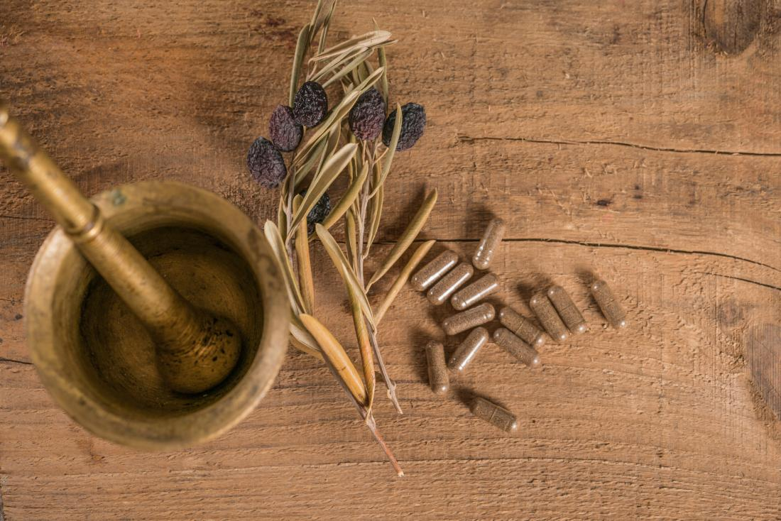 Olive leaf extract supplements on wooden table next to dried olive branch and pestle and mortar.