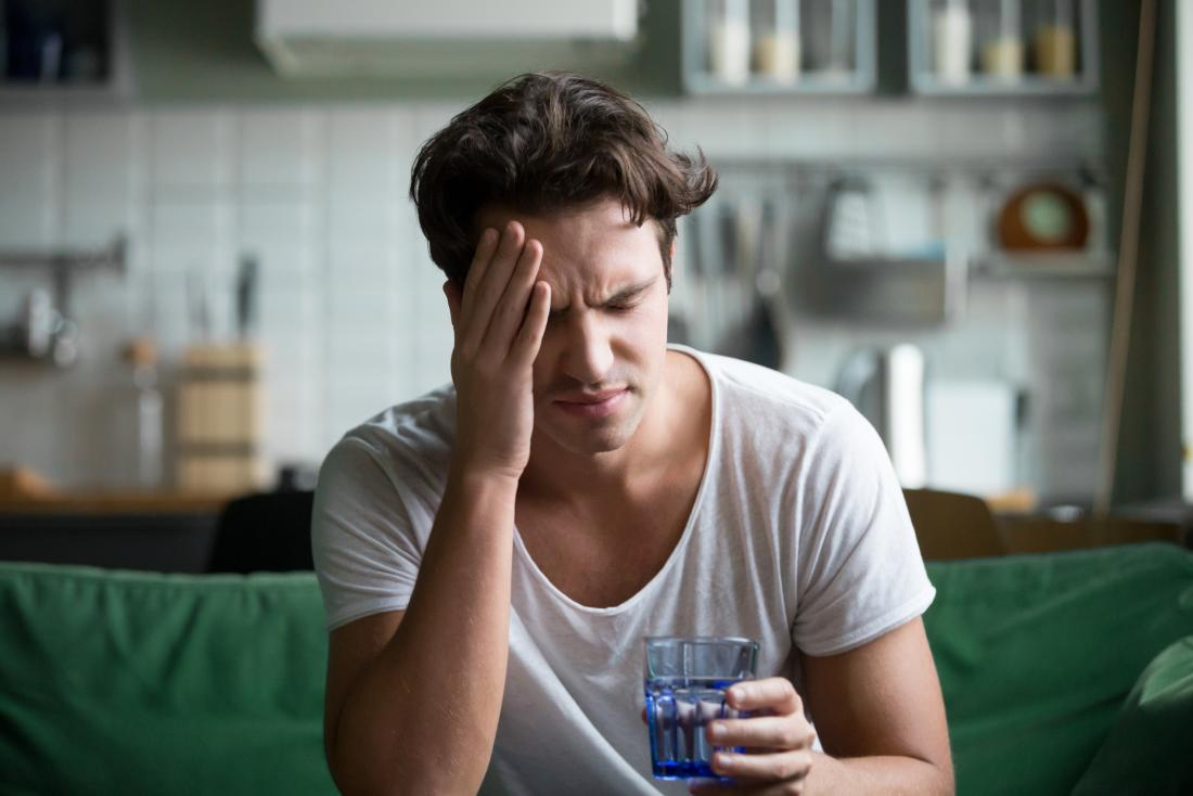 Man with hangover, nausea, headache or migraine holding head in pain and glass of water.