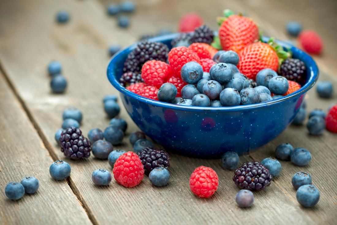 Bowl of fresh fruit and berries, including raspberries, blackberries, blueberries, and strawberries.