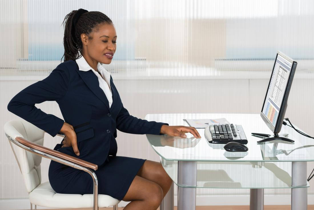 Woman with back pain at her computer due to poor posture