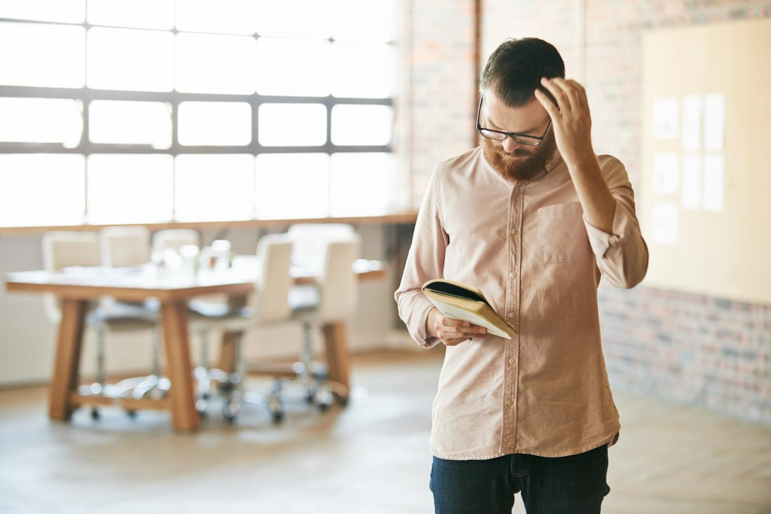 Man itching scalp or scratching head while reading book
