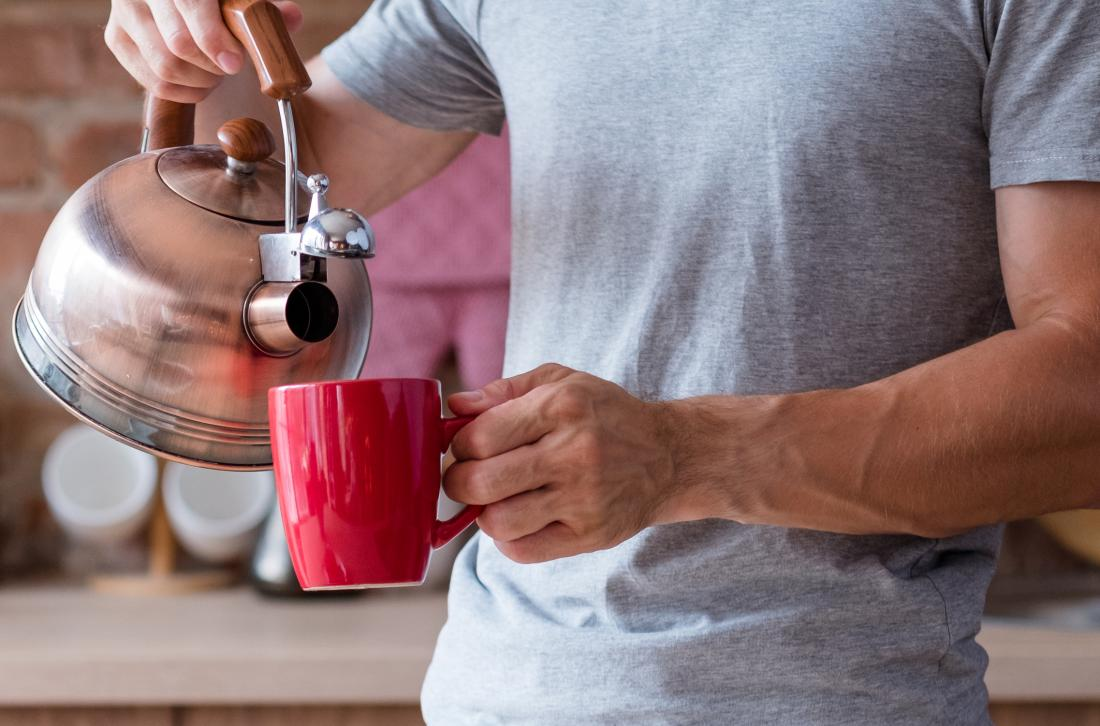 Person pouring hot or warm water from kettle into mug in kitchen