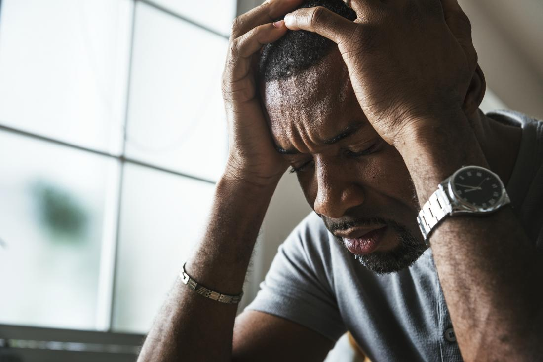 man holding his head in his hands, looking very stressed