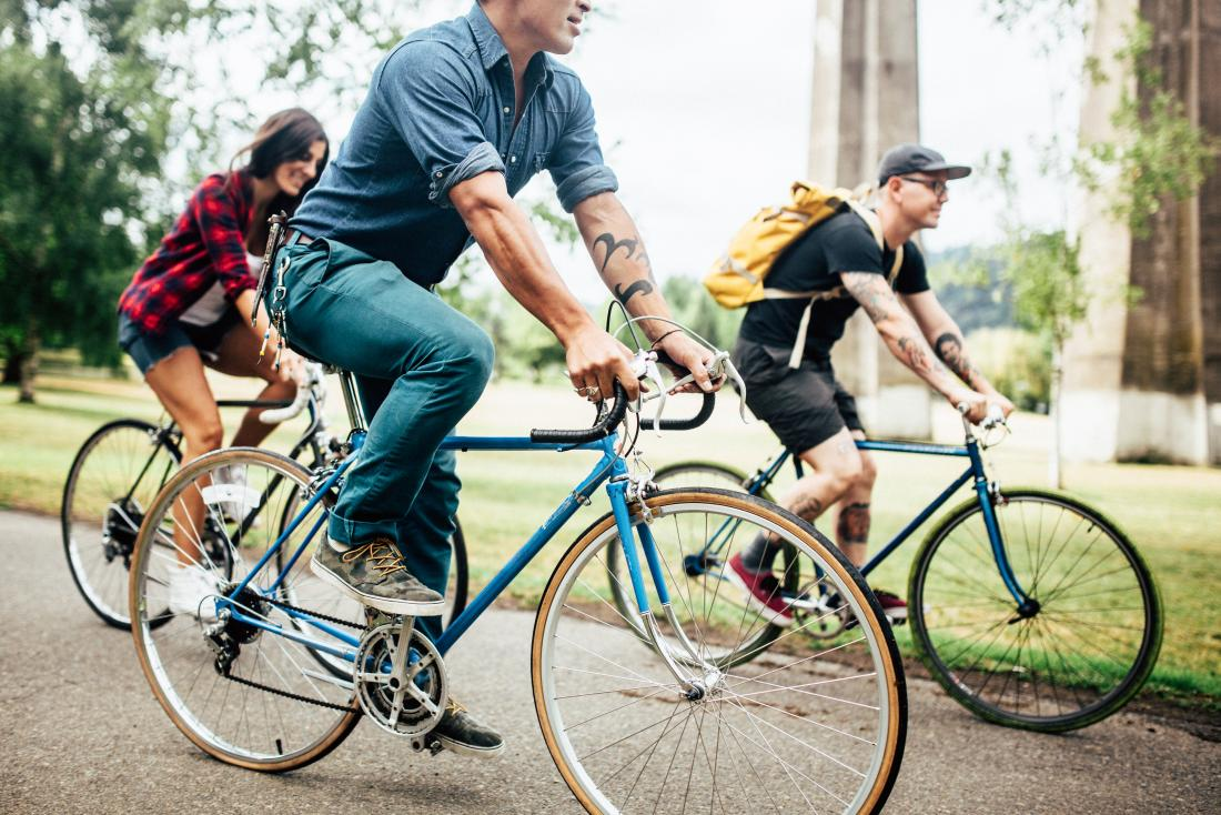 Group of friends cycling through park on bikes