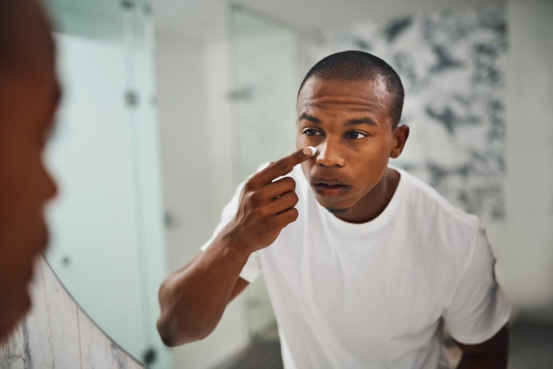 Black or african american man looking in bathroom mirror applying cream or lotion to skin under eyes.