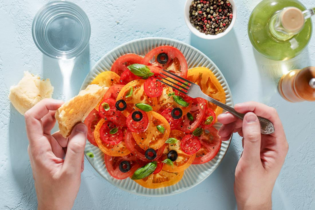 male hands eating tomato salad