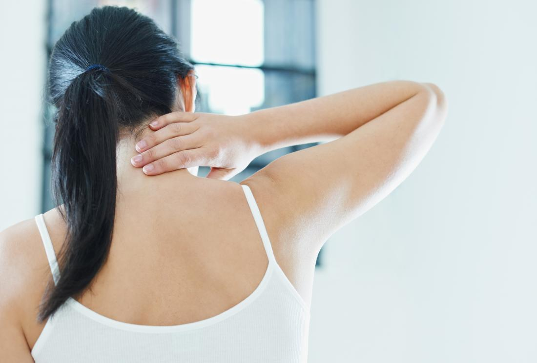 Woman holding back of neck and shoulder