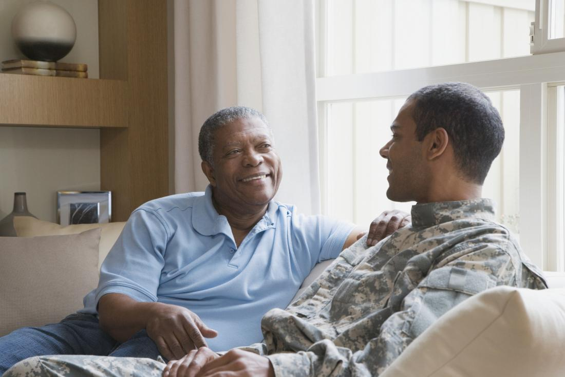 Senior african american black father with son in army uniform at home.