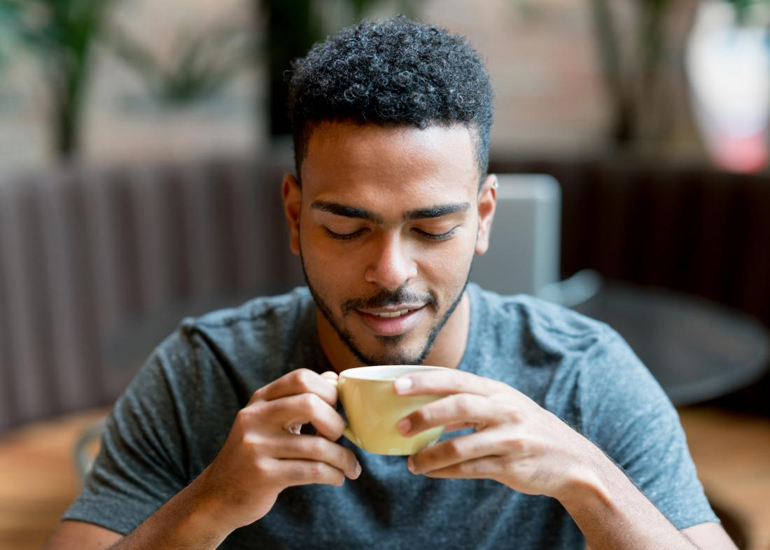man looking at coffee cup