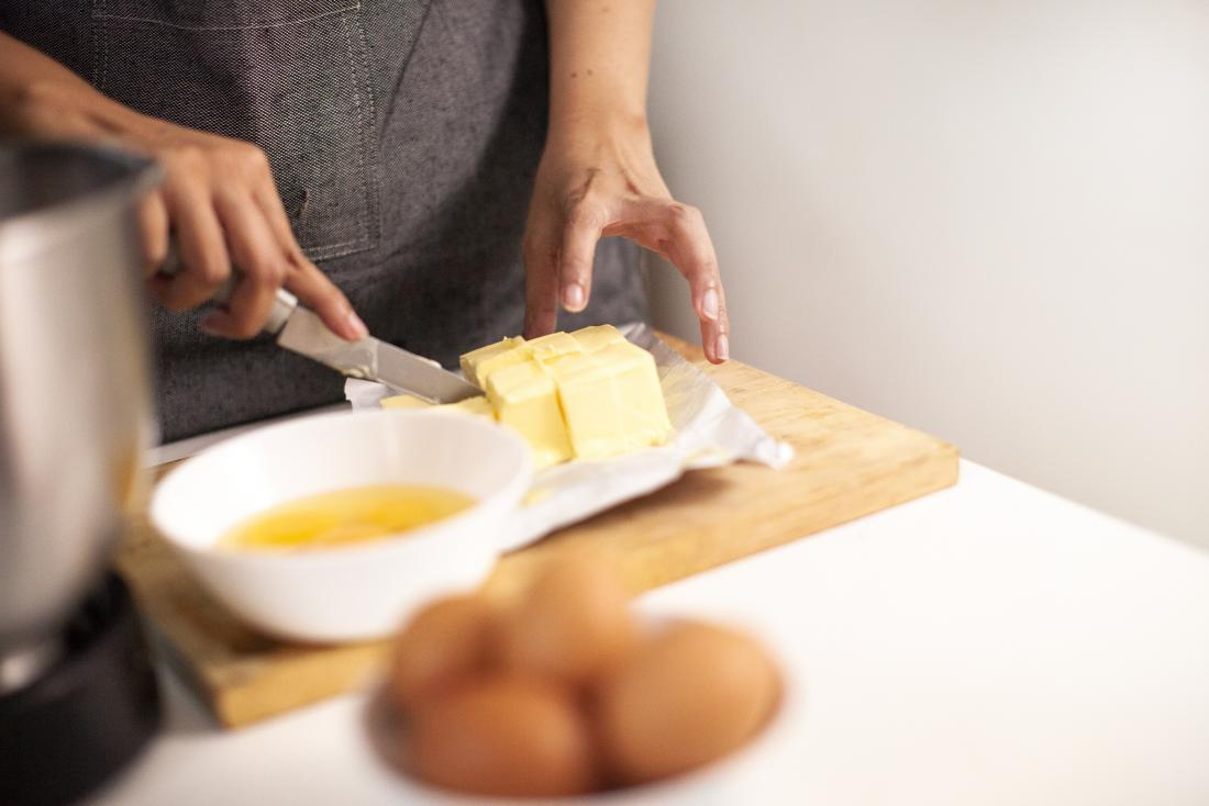 Person cutting up butter on wooden chopping board in kitchen with oil and eggs in the foreground.