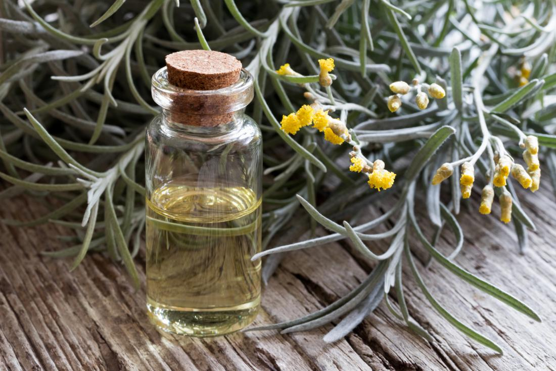 helichrysum essential oil in bottle next to plant on wooden table.