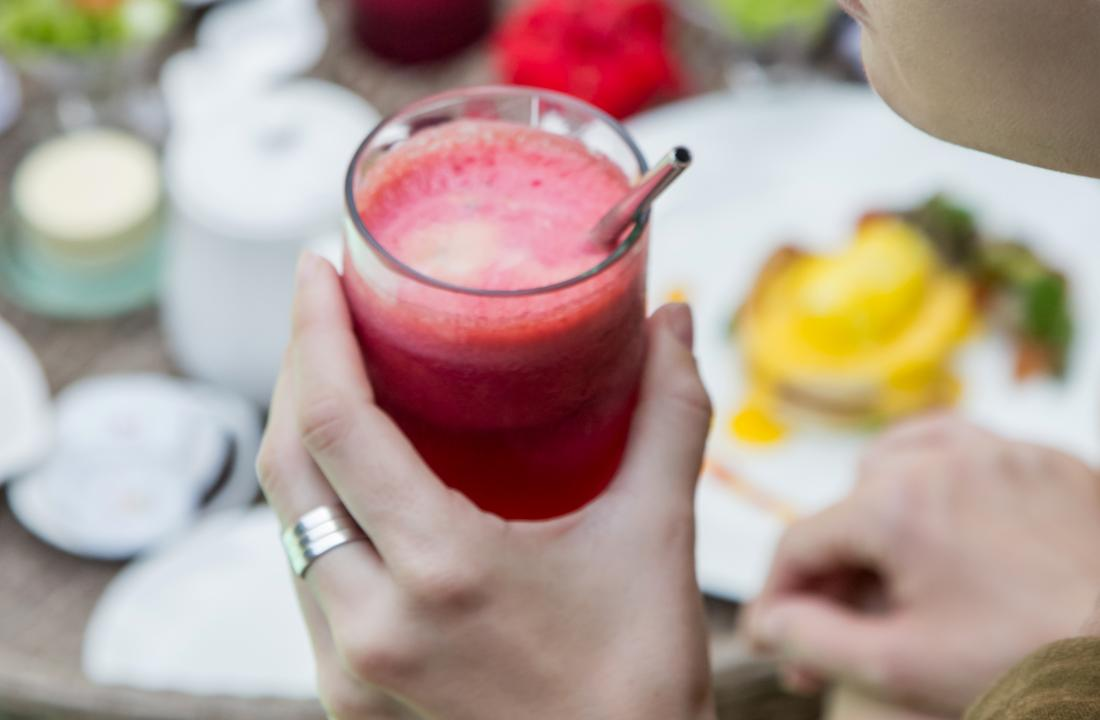person drinking smoothie or juice made of beetroot-or pomegranate at breakfast table.