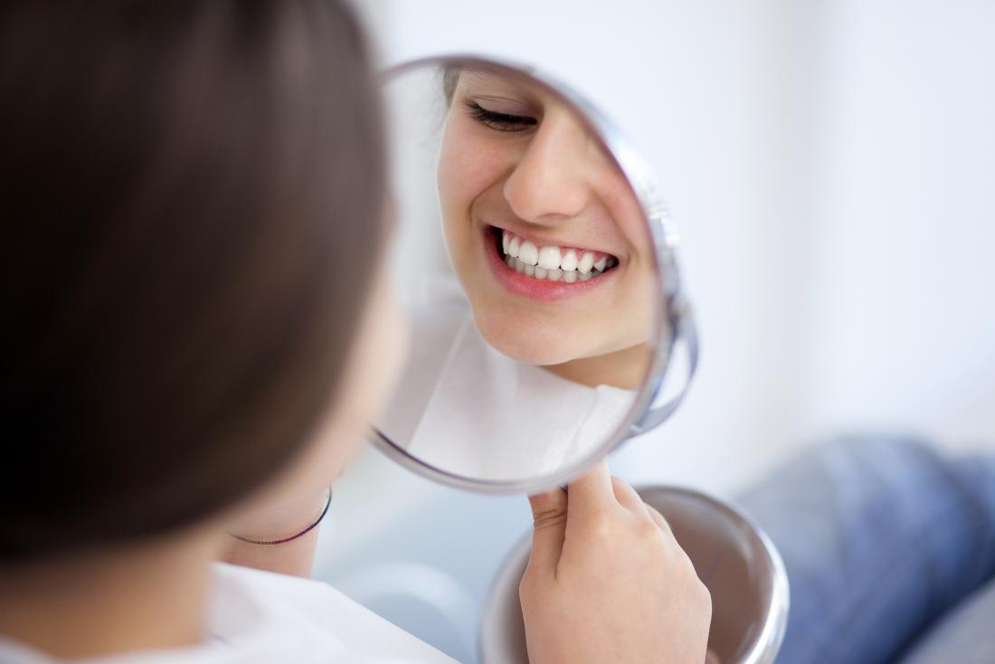 young woman looking at her teeth in mirror