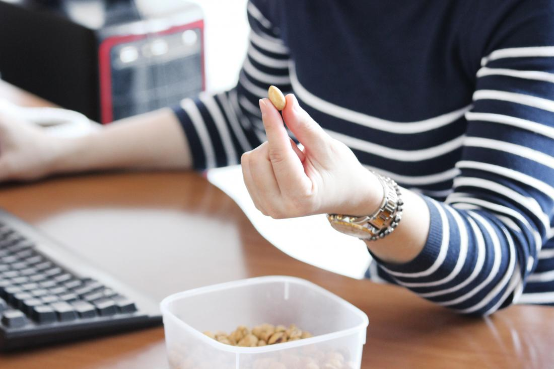 Woman at desk at work snacking and eating on peanut