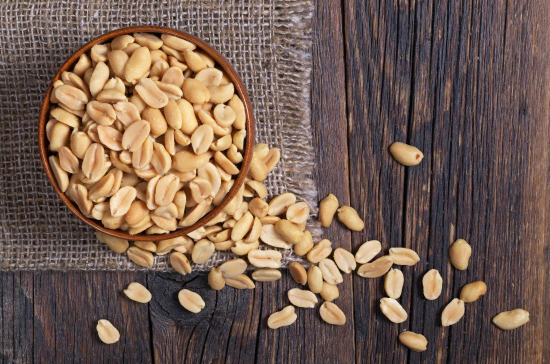Peanuts in a bowl on wooden table top down view.