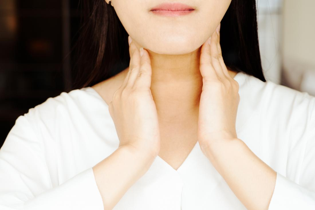 Woman holding her neck due to postnasal drip