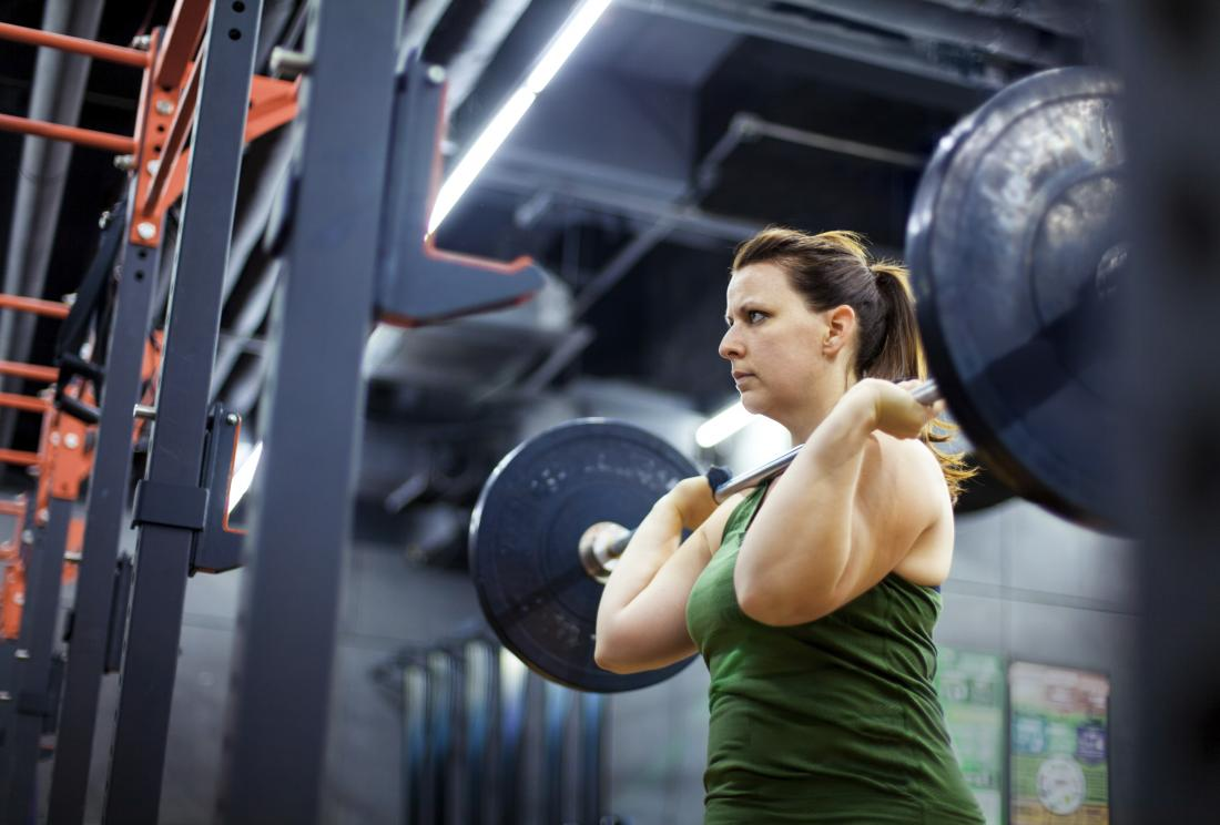woman lifting weights and bodybuilding in gym