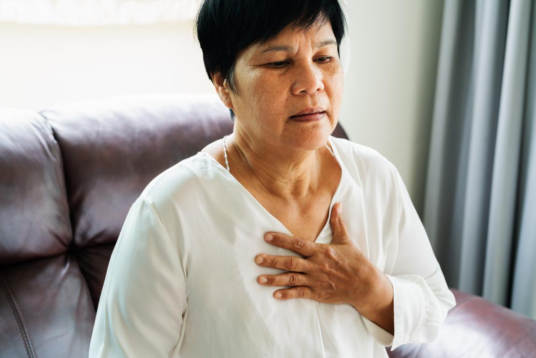 Mature asian woman holding hand to chest due to heart attack or breathing pain.