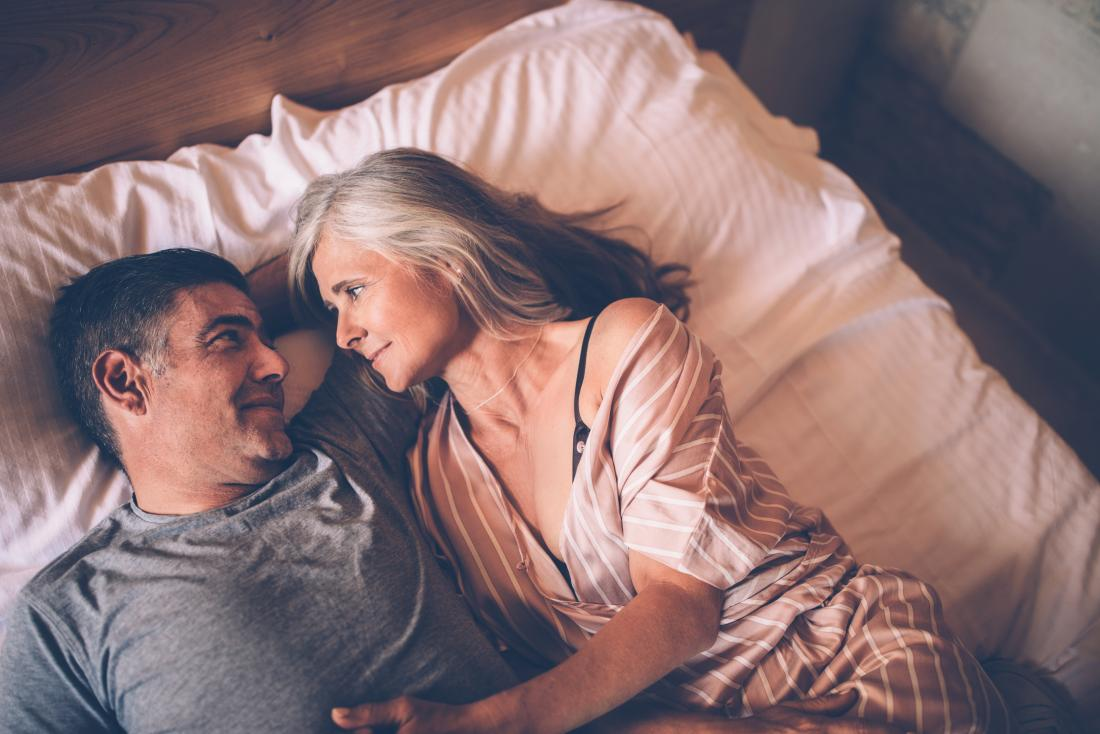 Mature couple experiencing loss of libido lying in bed looking at one another