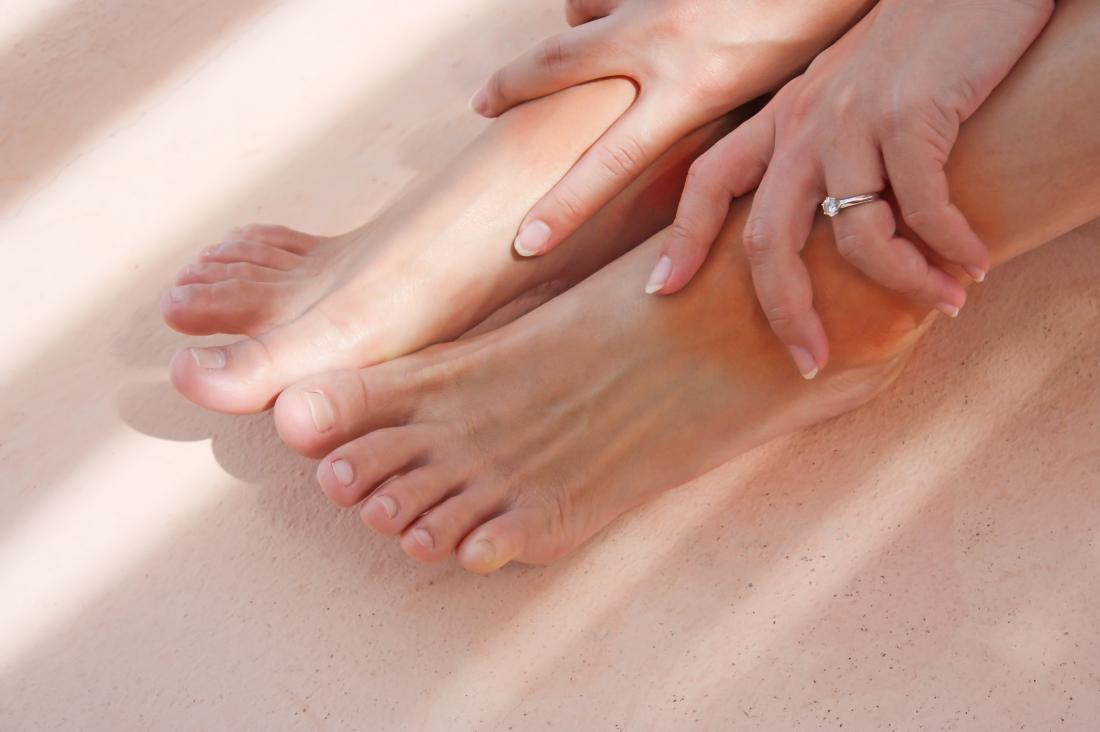 woman with bare feet and hands on her ankles