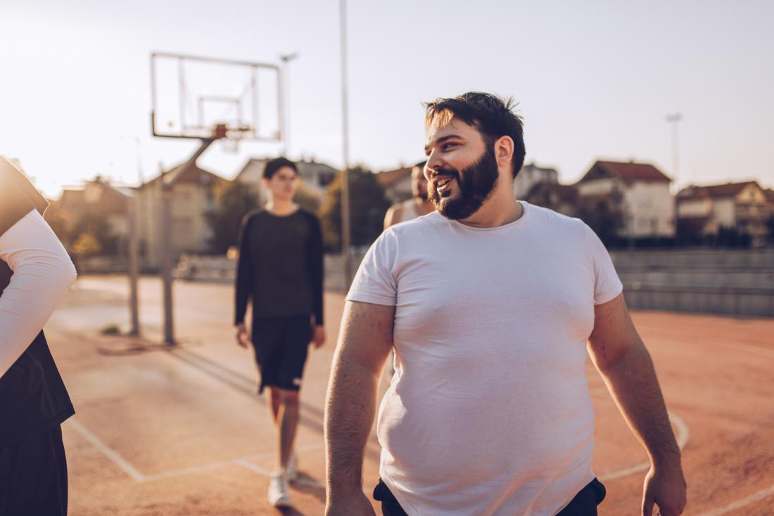 Overweight man outdoors playing basketball with friends smiling