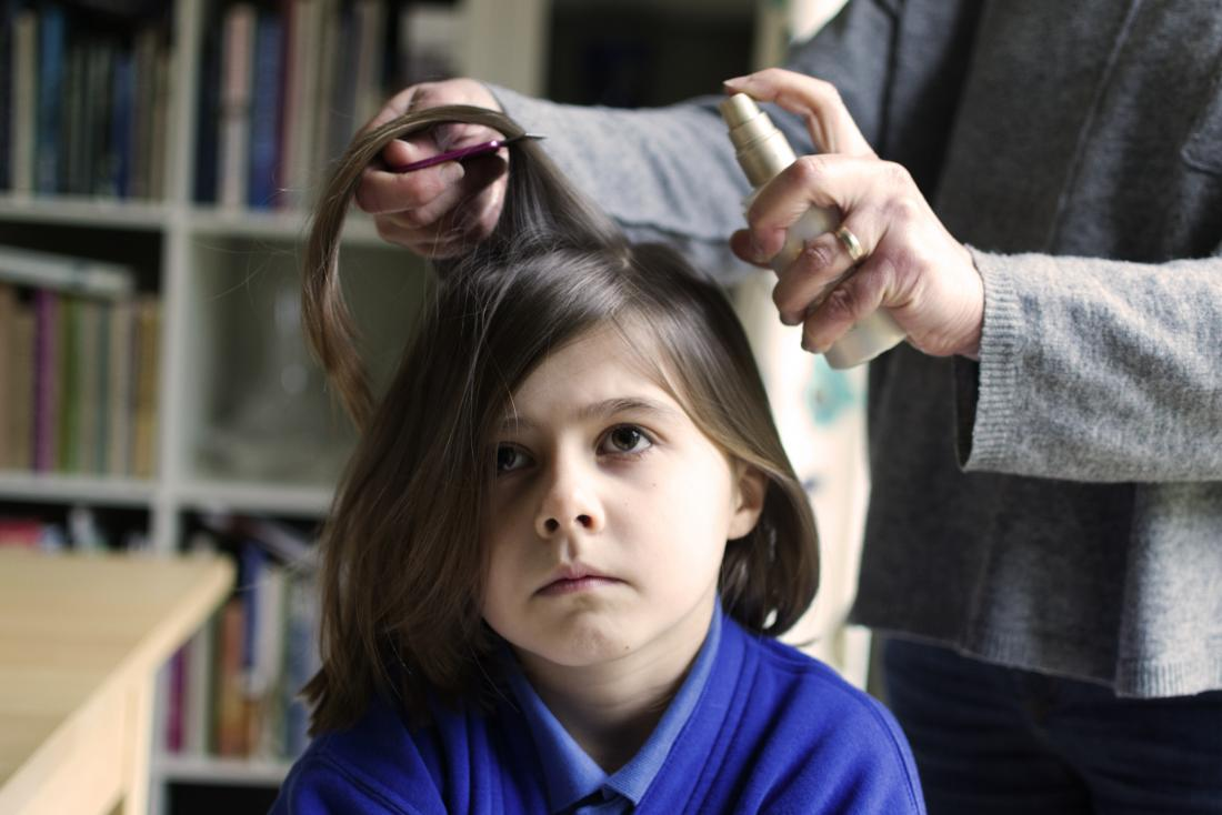 Head lice treatment being applied to a young girls hair