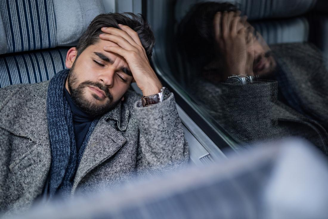 Man with headache or migraine holds head leaning against the vehicle window.