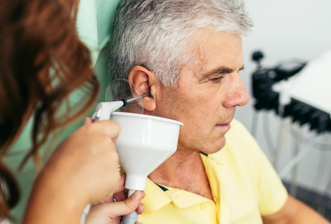 Man having ear irrigation performed