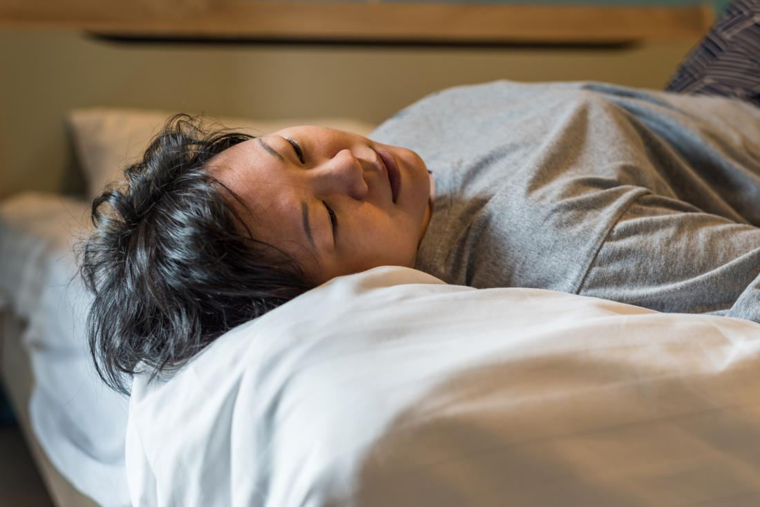 Mature woman lying on bed having sleep problems.